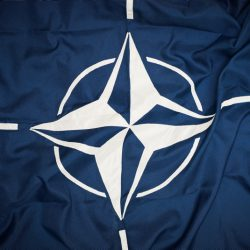 The flag of NATO.  The flag of the North Atlantic Treaty Organization (NATO) consists of a dark blue field charged with a white compass rose emblem, with four white lines radiating from the four cardinal directions.   Adopted three years after the creation of the organization, it has been the flag of NATO since October 14, 1953. The blue colour symbolizes the Atlantic Ocean, while the circle stands for unity.