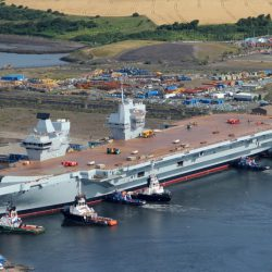The Royal Navy's largest ever warship HMS Queen Elizabeth is gently floated out of her dock for the first time in Rosyth, Scotland in July 2014.  In an operation that started earlier that week, the dry dock in Rosyth near Edinburgh was flooded for the first time to allow the 65,000 tonne aircraft carrier to float. It then took only three hours this morning to carefully manoeuvre HMS QUEEN ELIZABETH out of the dock with just two metres clearance at either side and then berth her alongside a nearby jetty.  Teams will now continue to outfit the ship and steadily bring her systems to life in preparation for sea trials in 2016.  The dock she vacates will be used for final assembly of her sister ship, HMS PRINCE OF WALES, which will begin in September.