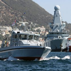 HMS DARING sailing into Gibraltar while HMS Scimitar from the Gibraltar Royal Naval Squadron provides security while she is within the British Gibraltar territorial waters.  The two Fast Patrol Boats of the Royal Navy's Gibraltar Squadron, HMS Sabre and HMS Scimitar, watch over Gibraltar's shores and support ships in the Strait of Gibraltar. The two boats, along with three Pacific Rigid Inflatable Boats, support British exercises and operations in the area.  HMS Daring, the first Type 45, is at the forefront of the Royal Navy's next generation of Area Air Defence Destroyers. At 151 metres long, weighing 8000 tonnes and packed with the latest in Air Warfare technology, Daring is a world leader and world beater.  Her highly trained complement of 190 Sailors is trained to act across the full spectrum of military activity; including such missions as Disaster Relief in the wake of a typhoon, Maritime Security operations to counter the threat from piracy, and when required, high intensity war fighting against the nation's enemies.